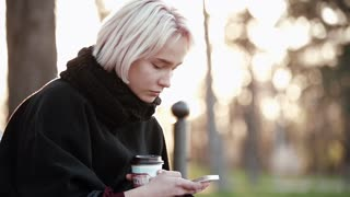 Blonde woman girl outside. In the hands of a smartphone and coffee. Sits on a wooden bench. Sadly reading the message on the smartphone.