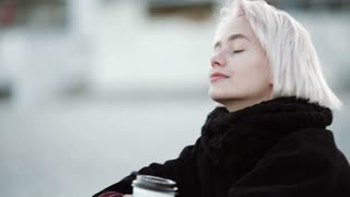 Blonde woman girl outside. On the public beach, he drinks coffee. Enjoys the sea breeze, looks into the distance, smiles. Dreams, thinks about the good. Close-up