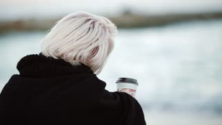 Blonde woman girl outside. On the public beach, he drinks coffee. He looks into the distance, calmly. Called her. Turns around, looks at the camera, smiles. View from the back. From the first person.
