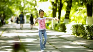 Little brunette girl doing somersault, upheaval, gymnastics in the park.