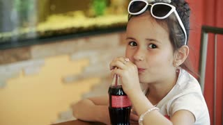 Little girl child brunette latina sitting in cafe, drinking soda cola. Against the backdrop of an aquarium with fish.