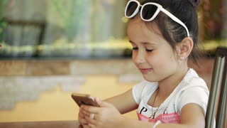 Little girl child brunette latina sitting in cafe, playing on smartphone in game, with serious face degeneration.