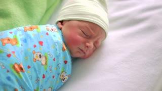 Newborn baby in hospital room. Infant sleeping in bedside bassinet. Little boy