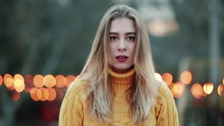 Portrait Beautiful girl blond young woman looks at the camera never taking her eyes off angry expression Emotionless Against the background of orange yellow lights The wind blows in the evening city.
