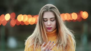 Portrait Blonde girl, a young woman adjusts her hair looking into the camera like in a mirror Dissatisfied with the state Against the background of orange yellow lights The wind blows in evening city