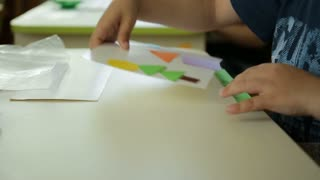 The child collects a color picture. Art handmade. Cut out shapes. Hands and table are large.