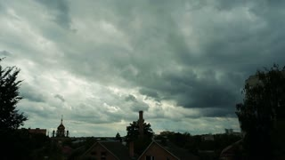 Timelaps. Stormy clouds over the city. Church, brick chimney. Dark, gray clouds quickly move, the rays can be seen.