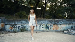 Young Asian woman dancing modern choreography in city park, outside. City ruins and graffiti. Direction is jazz-funk, hip-hop.