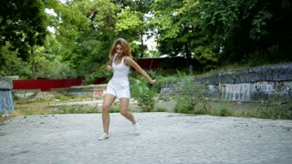 Young Asian woman dancing modern choreography in city park, outside. City ruins and graffiti. Hip-hop and jazz-funk