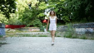 Young Asian woman dancing modern choreography in city park, outside. City ruins and graffiti. Hip-hop