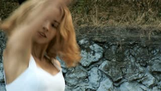 Young Asian woman dancing modern choreography in city park, outside. City ruins and graffiti. jazz-funk. Close-up. Slowmotion