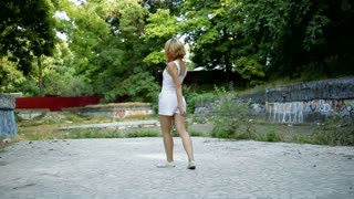 Young Asian woman dancing modern choreography in city park, outside. City ruins and graffiti jazz-funk