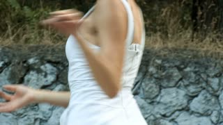Young Asian woman dancing modern choreography in city park, outside. City ruins and graffiti. Variety. Close-up. Slowmotion