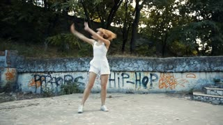 Young Asian woman dancing modern choreography in city park, outside. City ruins and graffiti. Variety