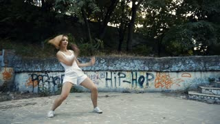 Young Asian woman dancing modern choreography in city park, outside. City ruins and graffiti. With elements of jazz, funk, hip-hop.