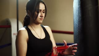 Young beautiful female latinos girl wraps her arms around a red elastic bandage, against the backdrop of a boxing pear
