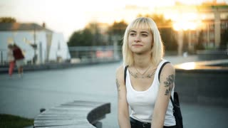 Young blond woman sitting on a wooden bench, waiting. She looks into the distance, on either side. Horizontal glare of the sunset light reflected from the glass showcase. straightens hair