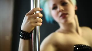 Young woman girl informal appearance dancing with pylon exotic Pole dance. Sexy blonde. Touching to caress the pylon