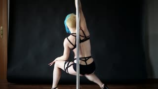 Young woman girl informal appearance dancing with pylon exotic Pole dance. Sexy blonde