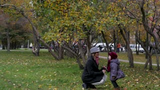 a little girl hit her mother in the autumn park. child aggression