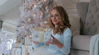 a young woman examines Christmas gifts and the interior of the house. bright Christmas interior