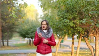 a young woman smokes on the background of a Park outdoor