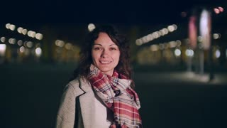 An attractive young woman acts a little shy then gives the camera a bit smile.
