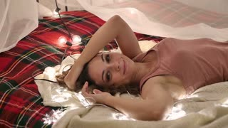 beautiful woman on the bed, christmas interior, enjoyment