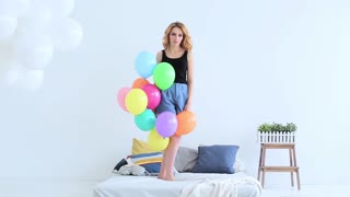 beautiful young woman jumping on the bed with balloons