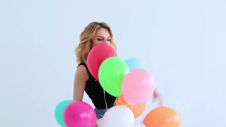 beautiful young woman smiling and holding balloons