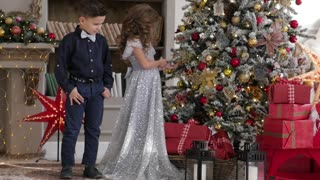 children dressed in elegant clothes adorn a tree of roses. festive mood