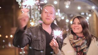 Couple with sparklers on the background of night city