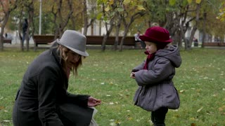 daughter with her mother collecting autumn leaves in the park