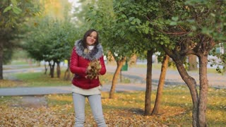 Fall woman happy throwing autumn leaves laughing