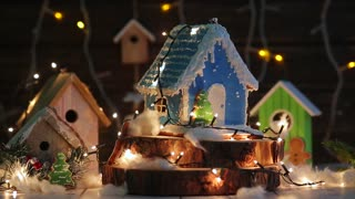 gingerbread house on the background of a garland and wooden houses. sprinkle with powdered sugar