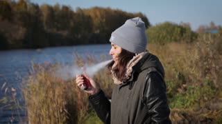Girls elegantly smokes an e-cigarette and blows smoke in the park portrait
