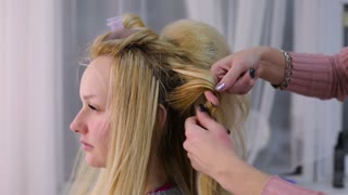 hairdresser at salon makes the client's hair. blonde client with long hair