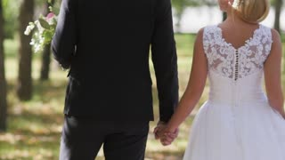 the bride and groom are walking in the park in anticipation of the wedding ceremony. holding on to the hand