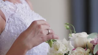 The bride is holding a wedding bouquet in her hands, fingering the flowers and sniffing it