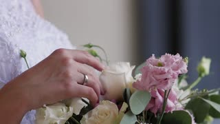 The bride is holding a wedding bouquet in her hands, fingering the flowers