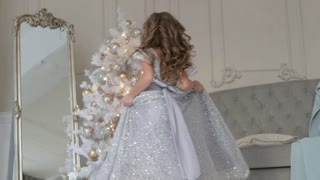 the girl is dancing in a beautiful shiny dress. Christmas interior