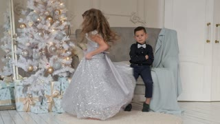 the girl is dancing in front of the boy in a beautiful dress. Christmas interior