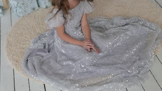 the girl is sitting in a beautiful shiny dress. Christmas interior