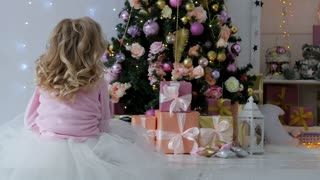 the girl sits on the floor of the house with Christmas gifts and a garland. The girl sits back