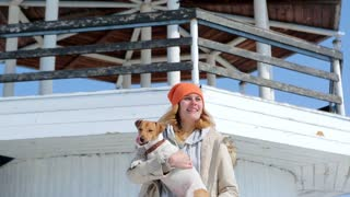 The girl with the dog on the background of the lighthouse.