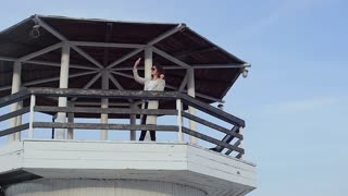 the young woman at the lighthouse. developing hair. slow motion
