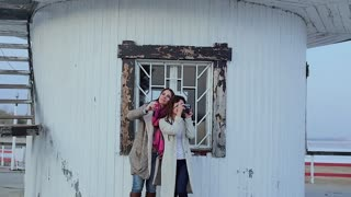 two young women are photographed on the background of the lighthouse. slow motion
