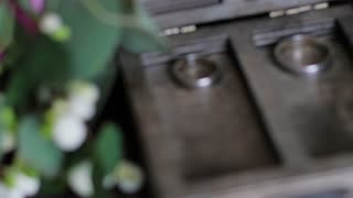 wedding rings lie in a wooden box. wedding bouquet on the background of rings. slow motion