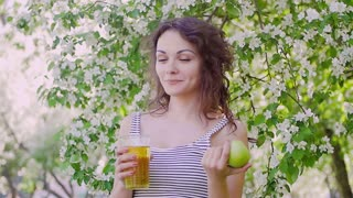 woman pouring juice from a jug on the background of Apple