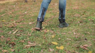 woman walking in autumnal park on orange leaves. Tracking shot. Low angle.